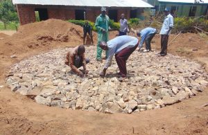 The Water Project:  Tying Wire On Top Of Rain Tank Stone Foundation