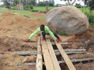 The Water Project:  Artisan Measures Latrine Foundation Over Pits