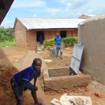 The Water Project: Mukama Primary School -  Boy Poses With Rain Tank In Progress