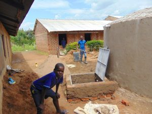 The Water Project:  Boy Poses With Rain Tank In Progress