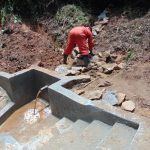 The Water Project: Kisasi Community, Edward Sabwa Spring -  Backfilling With Stones As Water Begins To Flow