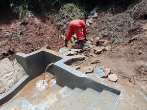 The Water Project:  Backfilling With Stones As Water Begins To Flow
