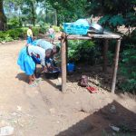 The Water Project: Shikomoli Primary School -  Students Help Wash Utensils At Dishrack