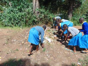 The Water Project:  Students Sweep Garbage Into Compost Pit