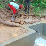 The Water Project: Kimarani Community, Kipsiro Spring -  Backfilling With Large Stones