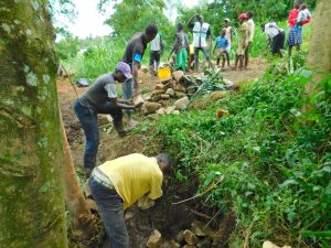 The Water Project:  Community Members Pass Stones For Backfilling