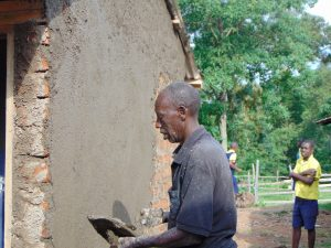 The Water Project:  Artisan Cements Latrine Walls As Student Looks On