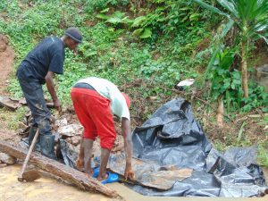 The Water Project:  Adding Thick Plastic Tarp Over Backfilled Stones