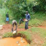 The Water Project: Shikhombero Community, Atondola Spring -  Backfilling With Rocks