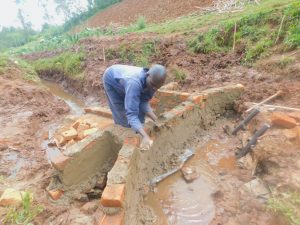 The Water Project:  Cementing Bricks Of Headwall Into Place