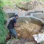 The Water Project: Buyangu Community, Mukhola Spring -  Adding Clay To Spring Box