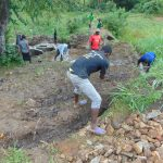 The Water Project: Buyangu Community, Mukhola Spring -  Digging Cut Off Drainage Above Spring