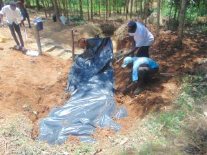 The Water Project:  Adding Tarp Over Stones