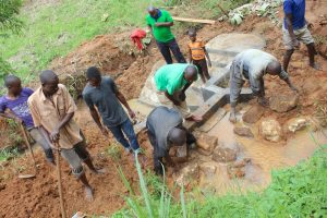 The Water Project:  Laying Stone Backfilling