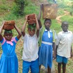 The Water Project: Bumira Community, Imbwaga Spring -  Kids Help Deliver Construction Materials