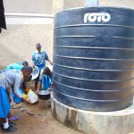The Water Project: Shikomoli Primary School -  Students Wash Dishes At Plastic Tank