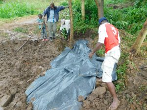 The Water Project:  Adding Tarp To Backfilling