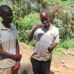 The Water Project: Kisasi Community, Edward Sabwa Spring -  A Man Demonstrates Toothbrushing Next To Trainer Amos