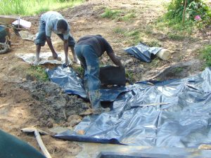 The Water Project:  Adding Tarp Over Backfill