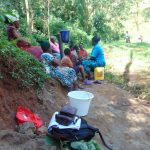 The Water Project: Bumira Community, Imbwaga Spring -  Karen Demonstrates Sitting On Open Water Container To Advise Against It