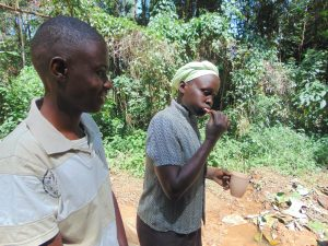 The Water Project:  A Woman Demonstrates Toothbrushing Next To Trainer Amos Misiko