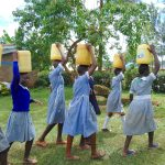 The Water Project: Saosi Primary School -  Students Carrying Water