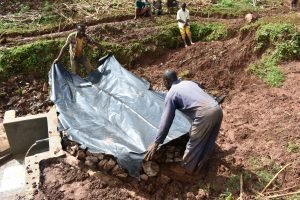 The Water Project:  Covering Backfilled Stones With Tarp