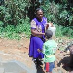 The Water Project: Kisasi Community, Edward Sabwa Spring -  Karen Squints In The Sun Helping A Boy Wash His Hands Using A Leaky Tin