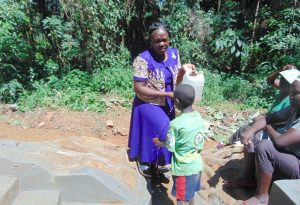 The Water Project:  Karen Squints In The Sun Helping A Boy Wash His Hands Using A Leaky Tin