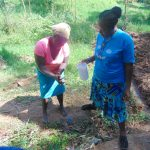 The Water Project: Bumira Community, Imbwaga Spring -  A Volunteer Demonstrates Handwashing