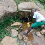 The Water Project: Galona Primary School -  Pupil Fetching Water