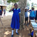 The Water Project: Mukama Primary School -  A Student Demonstrates Toothbrushing
