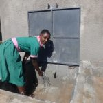 The Water Project: Mwichina Primary School -  Student Enjoying The Rain Tank Water