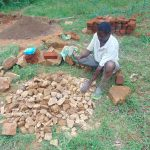 The Water Project: Bumira Community, Imbwaga Spring -  Community Member Breaks Rocks Into Gravel