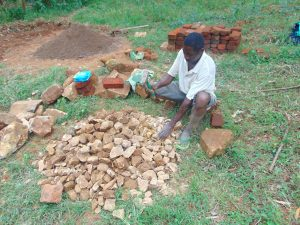 The Water Project:  Community Member Breaks Rocks Into Gravel