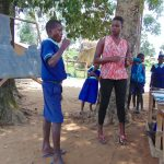 The Water Project: Mukama Primary School -  Student Demonstrates Toothbrushing