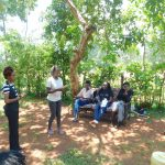 The Water Project: Shikhombero Community, Atondola Spring -  A Participant Makes A Presentation Next To Trainer Betty