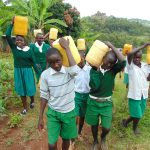 The Water Project: Galona Primary School -  Pupils Carrying Water