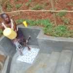 The Water Project: Bumira Community, Imbwaga Spring -  Spring Landowner Stellah Khalawa Washes Her Container Before Fetching Water