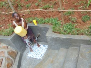 The Water Project:  Spring Landowner Stellah Khalawa Washes Her Container Before Fetching Water
