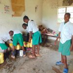 The Water Project: Galona Primary School -  Pupils Combine Water In A Pot