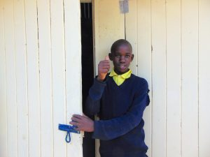 The Water Project:  Boy Stands In Front Of New Latrine Doors