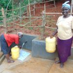 The Water Project: Jivovoli Community, Magumba Spring -  Women Fetching Clean Water