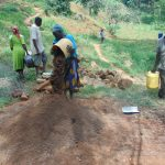 The Water Project: Bumira Community, Imbwaga Spring -  Community Members Delivering Local Materials To Site