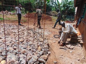 The Water Project:  Fitting Rebar To Stone Foundation
