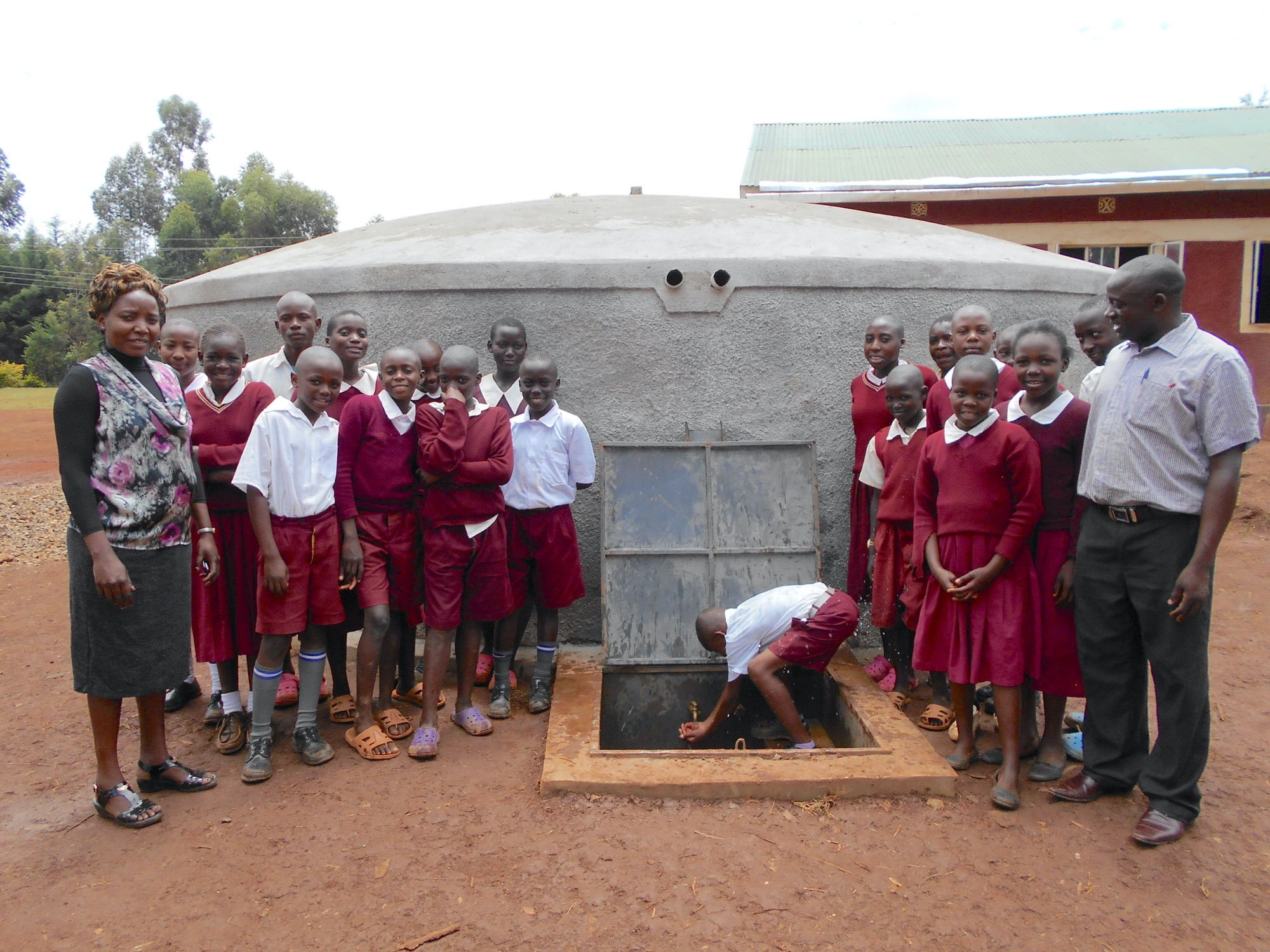 The Water Project : 44-kenya19062-students-and-teachers-pose-with-the-rain-tank