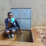 The Water Project: Kerongo Secondary School -  Student Drinks Water From The Rain Tank