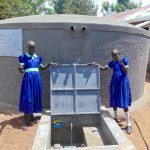 The Water Project: Mukama Primary School -  Girls Pose With The Rain Tank
