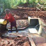 The Water Project: Shikhombero Community, Atondola Spring -  Rinsing Container Before Fetching Water