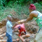 The Water Project: Kisasi Community, Edward Sabwa Spring -  Community Members Help Pass Bricks To The Artisan